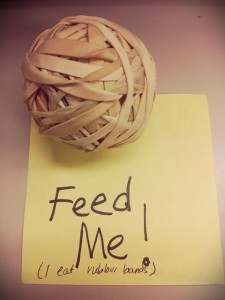 "Rubber band ball on a post it note that says ""Feed Me! I eat rubber bands."""