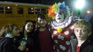 Kids posing with a scary clown outside of haunted firehouse