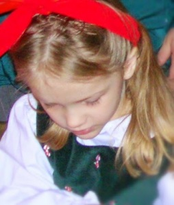 Girl in Christmas dress looking down at gift
