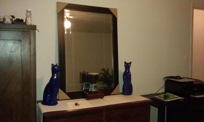 blue glazed cat figures on a dresser