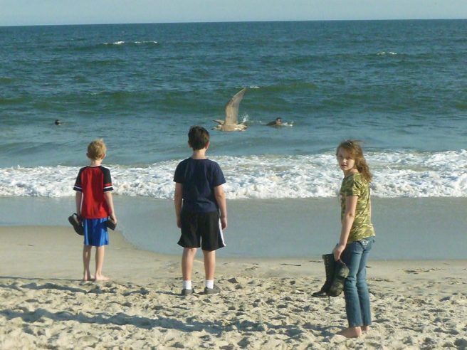 Three kids stand upon the shore