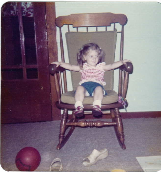 Me as a very little girl, sitting in a rocking chair