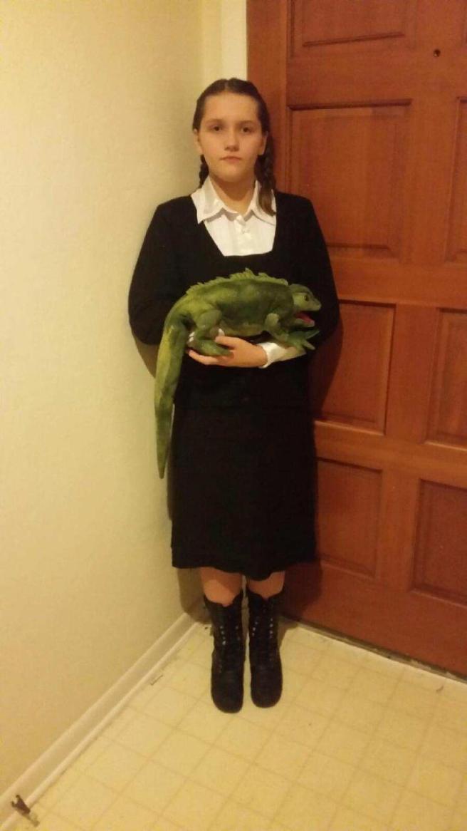Girl dressed like Wednesday Addams, holding iguana puppet