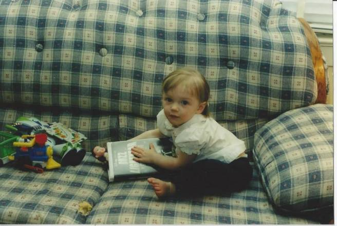 Toddler sitting on a couch with book and toys