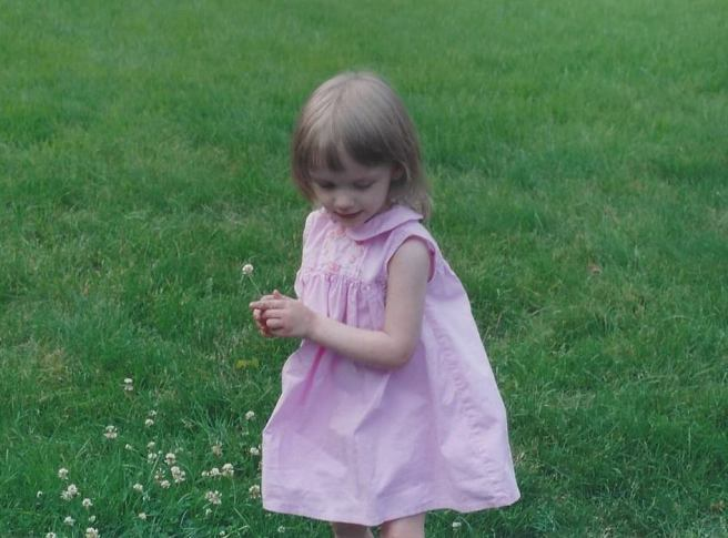 Girl in pink dress picking clover blossoms