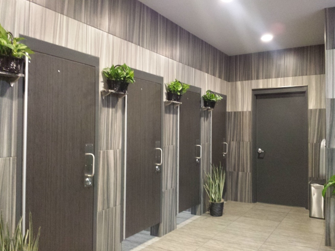 Bathroom stalls with plants hung everywhere