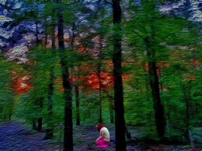 Girl kneeling in surreal landscape