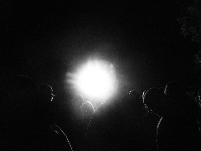 Black and white photo of people with light in background.