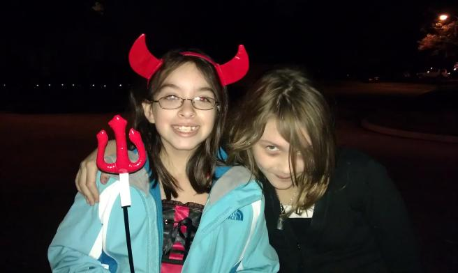 Girl with devil horns next to zombie girl