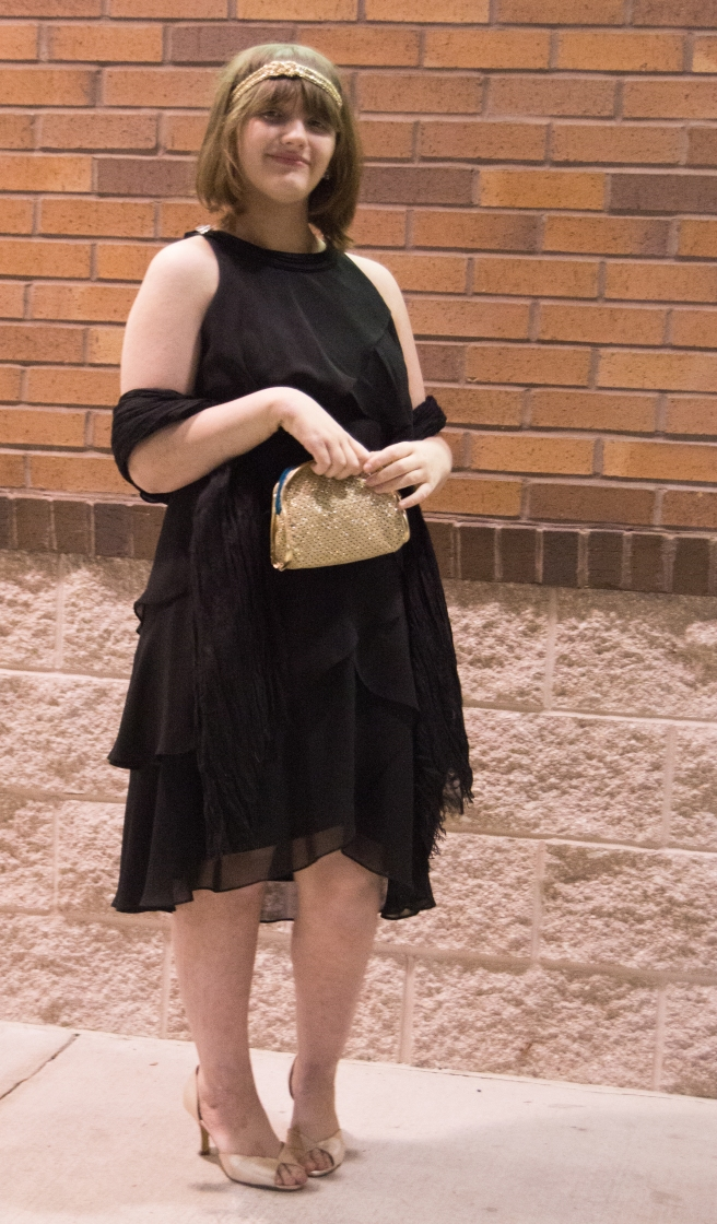 Flapper girl in black dress with gold accessories