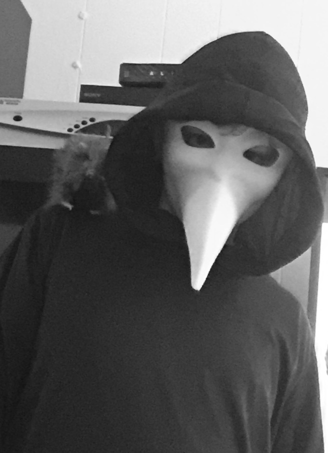 Boy in black hooded robe with White bird mask